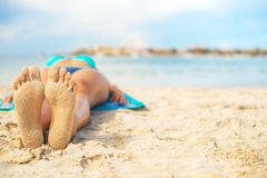 Woman sunbathing on sand. Stock Images