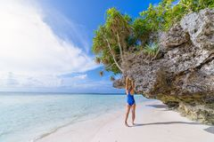 Woman sunbathing on scenic white sand beach, rear view, sunny day, turquoise transparent water, real people. Indonesia, Wakatobi stock photo