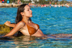 Woman is sunbathing in a sea Stock Images