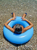 Woman sunbathing on  shore of  sea in an inflatable donut Royalty Free Stock Photos