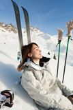 Woman sunbathing on a ski slope. Relaxed woman sunbathing in the snow in the ski slope Stock Photography