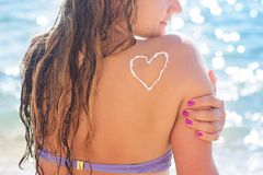 Woman is sunbathing with sunscreen tan lotion on Stock Photos