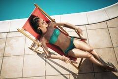 Woman sunbathing at swimming pool. During summer stock photo
