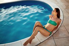 Woman sunbathing at swimming pool. During summer royalty free stock image