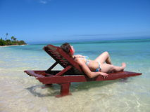 Woman sunbathing in a teak chair Royalty Free Stock Photography