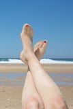 Woman sunbathing on tropical beach. Legs. Royalty Free Stock Photos