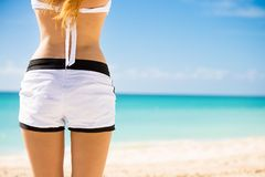 Woman sunbathing at tropical beach looking view of ocean on hot summer day Stock Photo