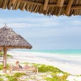 Woman sunbathing on tropical beach. Stock Photos