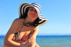 Woman sunbathing & wearing sun hat a the beach Stock Photos