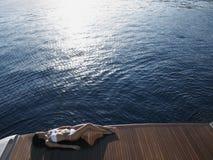 Woman Sunbathing On Yacht's Floorboard By Sea. High angle view of woman in bikini sunbathing on yacht's floorboard by sea Stock Photo