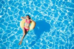 Woman sunbathing on yellow rubber ring in the pool. Attractive slim woman in pink bikini and sunglasses sunbathing on yellow rubber ring in the swimming pool stock image