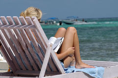Woman in sunbed - Belize. A blond woman reading a book in a sunbed at the seaside Royalty Free Stock Images