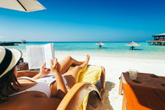 Woman on sunbed reading book under parasol at tropical island Stock Photos