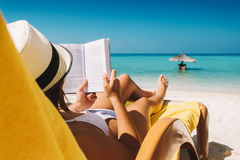 Woman on sunbed reading book under parasol at tropical island Royalty Free Stock Photos