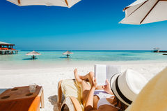 Woman on sunbed reading book under parasol at tropical island Royalty Free Stock Images