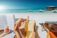 Woman on sunbed reading book under parasol at tropical island Stock Images