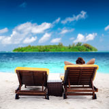 Woman on sunbed at tropical beach. Near green island Royalty Free Stock Photography