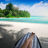 Woman on sunbed under palm tree Stock Photo