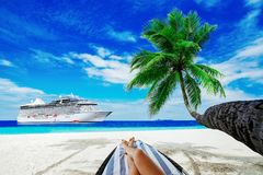 Woman on sunbed under palm tree. Cruise liner on sea. Travel background Royalty Free Stock Image