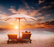 Woman on sunbed under umbrella at sunrise. Woman on sunbed under umbrella at sunset Royalty Free Stock Photos