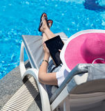 Woman on sunbed. Waering beautiful pink hat Royalty Free Stock Images