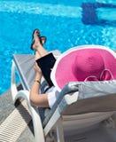 Woman on sunbed. Waering beautiful pink hat Stock Image