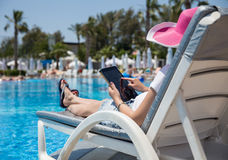 Woman on sunbed. Waering beautiful pink hat Royalty Free Stock Photography