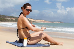 Woman with sunblock on the beach Stock Images