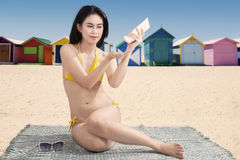 Woman with sunblock and the beach huts Stock Photos