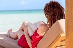 Woman on a sunchair reading a book in a tropical location. Clear turquoise water as background royalty free stock photography