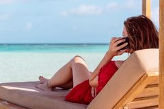 Woman on a sunchair in a tropical location calling friends with smartphone. Clear turquoise water as background stock photos