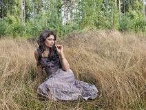 The woman in a sundress. Sits in not oblique grass Stock Photography
