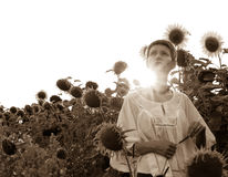 Woman with sunflowers. Portrait of a Romanian woman in a sunflower field Royalty Free Stock Images