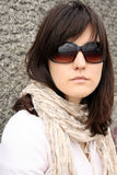 Woman in sunglasses. On background of stony wall. She wearing in scarf Royalty Free Stock Photography