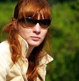 Woman in sunglasses. Portrait of attractive young woman with long red hair and sunglasses; green nature background stock photo