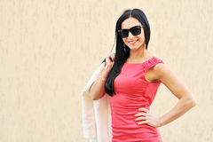 Woman in sunglasses against an orange background. Confident woman in sunglasses against an orange background royalty free stock image