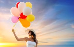 Woman in sunglasses with balloons over sunset sky Stock Photo