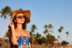 Woman in sunglasses on a beach. Beach vacation. A beautiful woman in sunglasses and sunhat standing on a blue sky and palms background Royalty Free Stock Photo