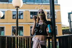 Woman in sunglasses blowing soap bubbles outdoors Royalty Free Stock Image