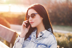Woman in sunglasses calling by phone in sunset Stock Images