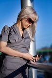 Woman in sunglasses with cellphone walking Royalty Free Stock Image