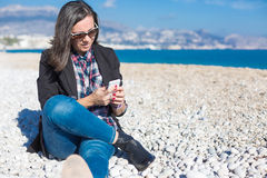 Woman in sunglasses chatting over phone sitting on beach Stock Photos