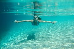 Woman diving swimming underwater view. Woman in sunglasses diving on a breath hold swimming under water view royalty free stock images