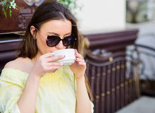 Woman in sunglasses drink coffee outdoors. Girl relax in cafe cappuccino cup. Caffeine dose. Coffee for energetic royalty free stock image