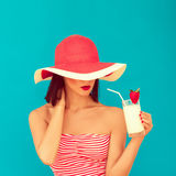 woman with sunglasses drinking a cocktail