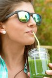 Woman with sunglasses drinking green vegetable Royalty Free Stock Image