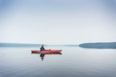 Woman in sunglasses enjoying the lake from red kayak Stock Images