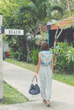 Woman in sunglasses with fashion snakeskin python bag walking on the street. Bali island, Indonesia. Stock Photo