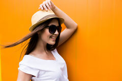 Woman in sunglasses and hat over orange colorful background Stock Images