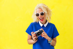Woman with sunglasses holding camera in her hands Royalty Free Stock Photography